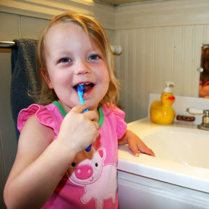 Young girl brushing her teeth